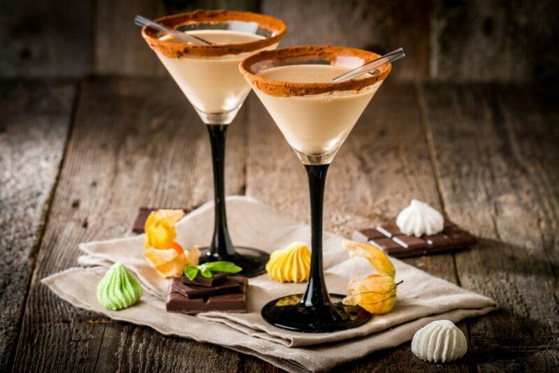 Two cocktail glasses containing Baileys Apple Pie Liqueur with some treats or candies on the table around the base of the glasses