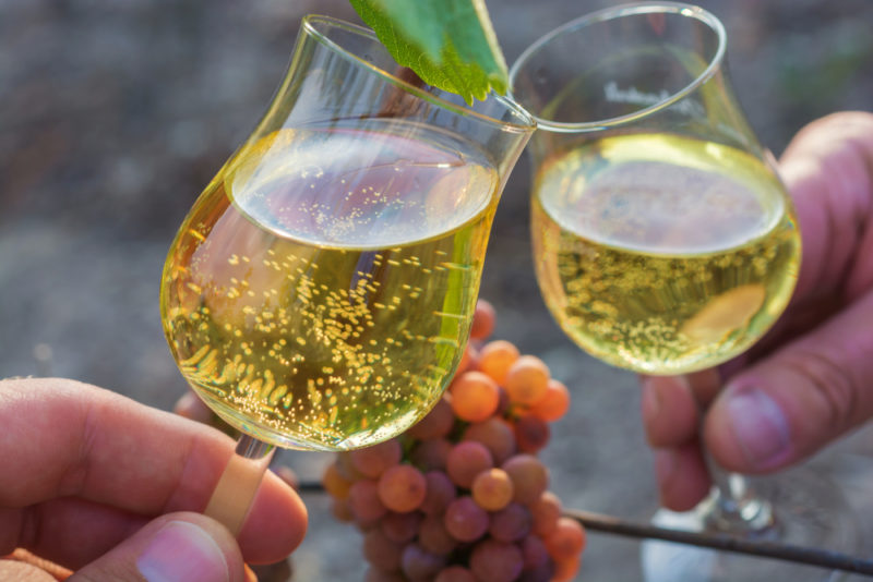 Two people toasting with glasses of Gewürztraminer