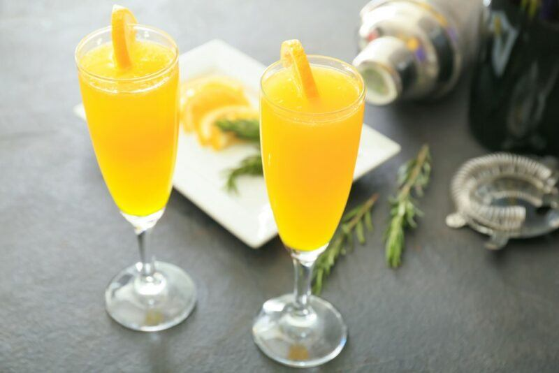 Two glasses of a bucks fizz cocktail in front of ingredients and a cocktail shaker