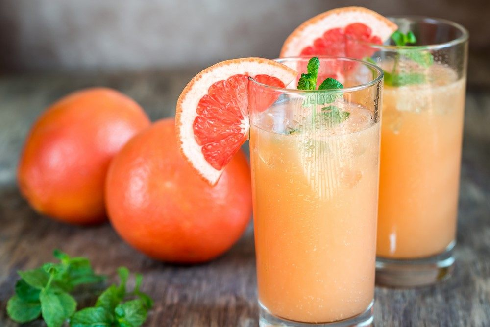 Two glasses of a palmoa cocktail next to grapefruit