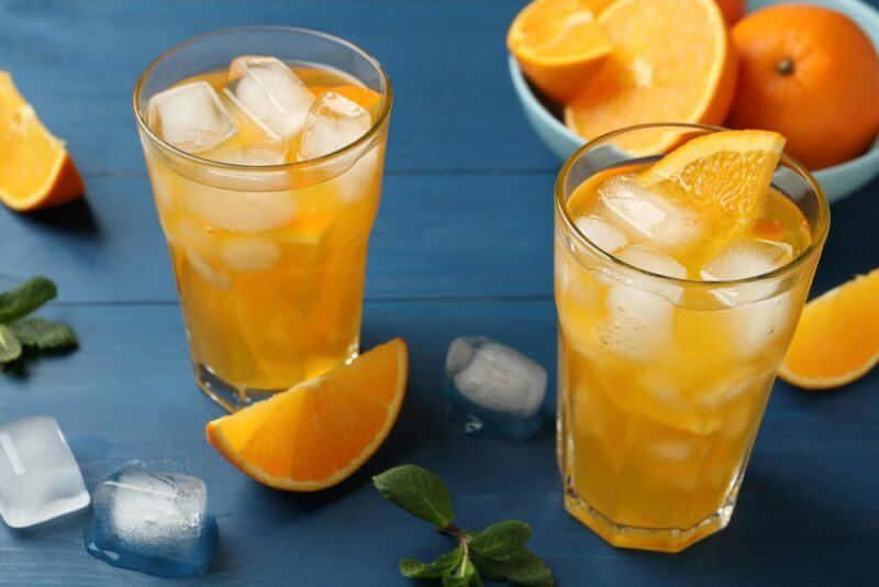 Two glasses of a sunflower highball cocktail with ice next to a bowl of oranges