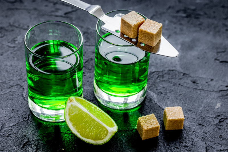 Two glasses of green absinthe with cubes of brown sugar and a wedge of lime