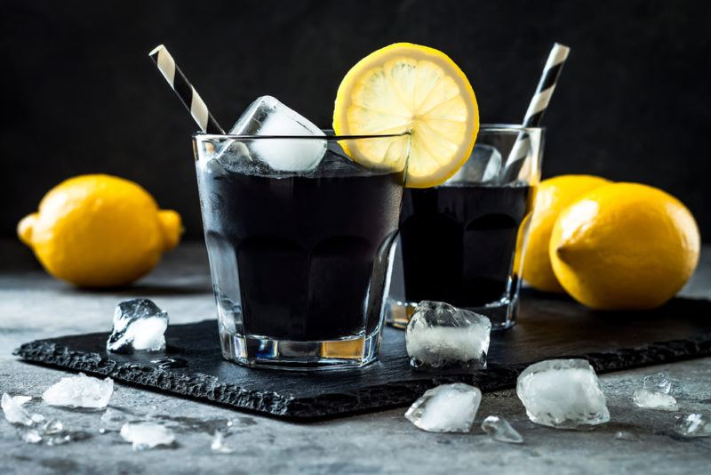 Two cocktails made with squid ink with straws, ice, and lemons