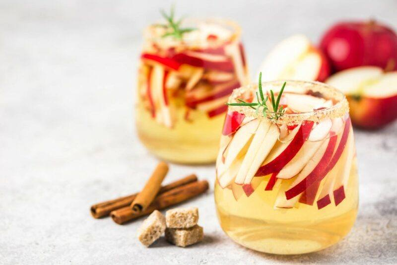Two glasses containing an apple and gin autumn cocktail, which include strips of apple as a garnish. There are some apples in the background, as well as cinnamon sticks and sugar cubes on the table