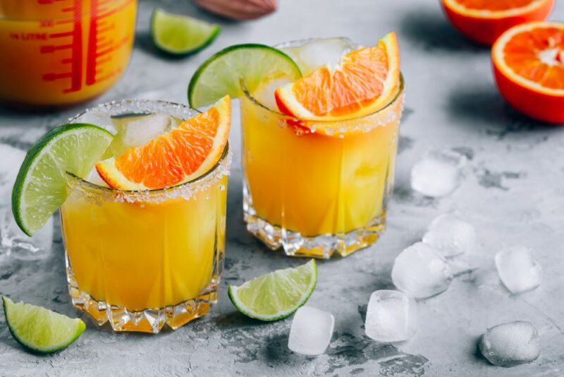 Two glasses of an orange margarita on a table with ice. The glasses each have a wedge of lime and one of orange.