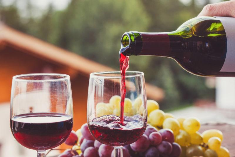 Two glasses of cabernet franc being poured from a bottle with green and red grapes outside