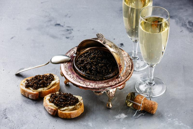 Two glasses of champagne next to caviar