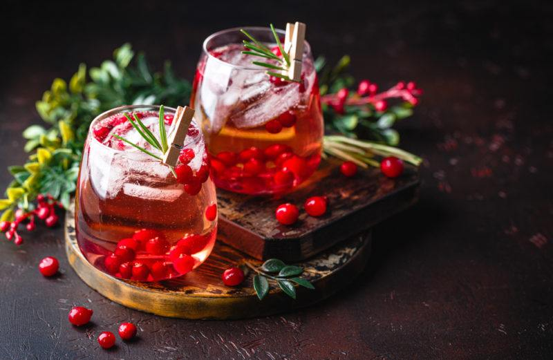 Two glasses of cranberry rum punch on a dark table