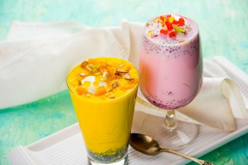 A glass of pink falooda and one of yellow falooda on a white dish and a green table