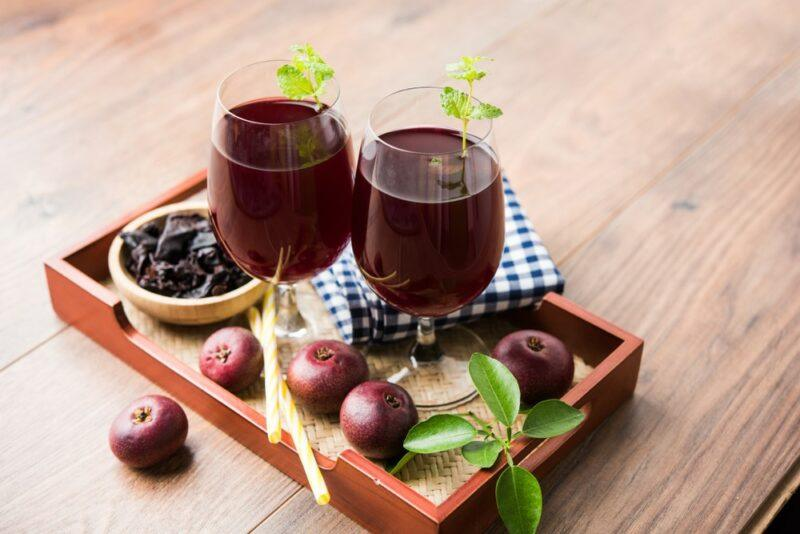 A wooden board with two glasses of kokum sherbet, with a bowl of the fruit and individual pieces of kokum fruit