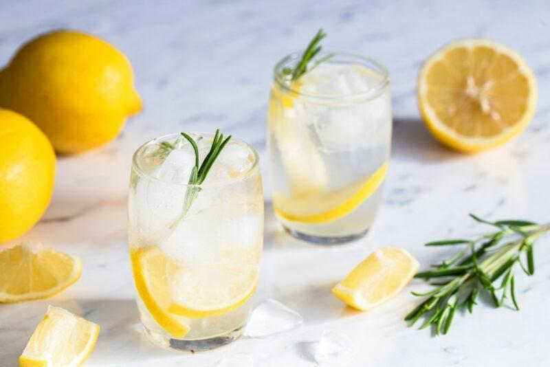 Two glasses of lemon and tonic water on a light colored table with lemons and rosemary nearby