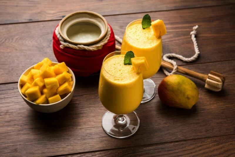 Two glasses of mango lassi on a wooden table, next to a pot and a bowl of mango pieces