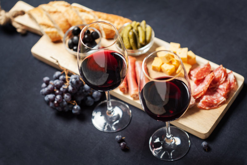 Two glasses of merlot wine on a black background next to a wooden board with various meats, cheeses, and other ingredients