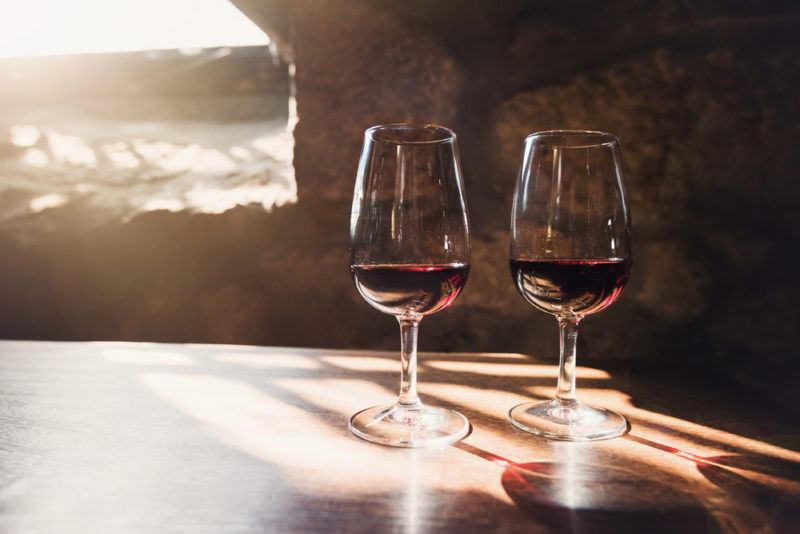 Two glasses of port in an underground room with sunlight streaming in from a window