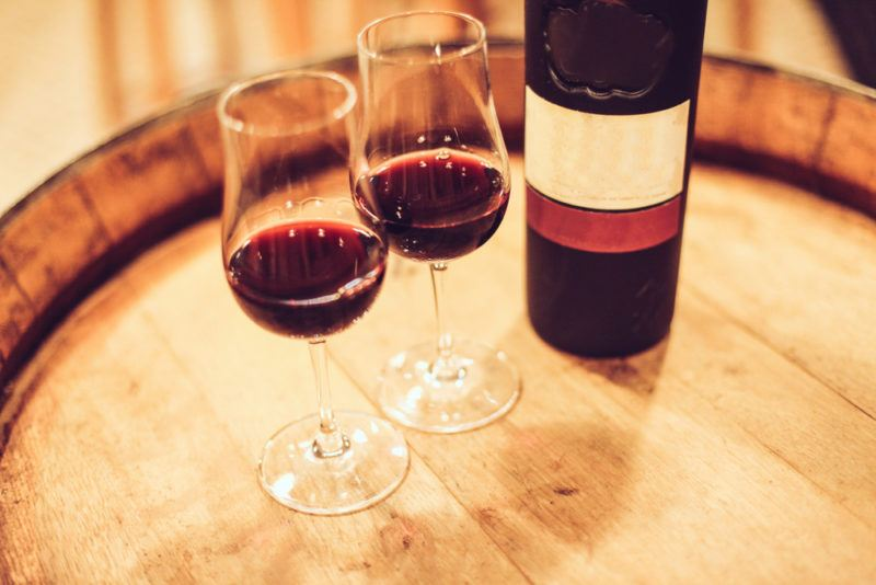 Two glasses of port next to a bottle on a barrel top
