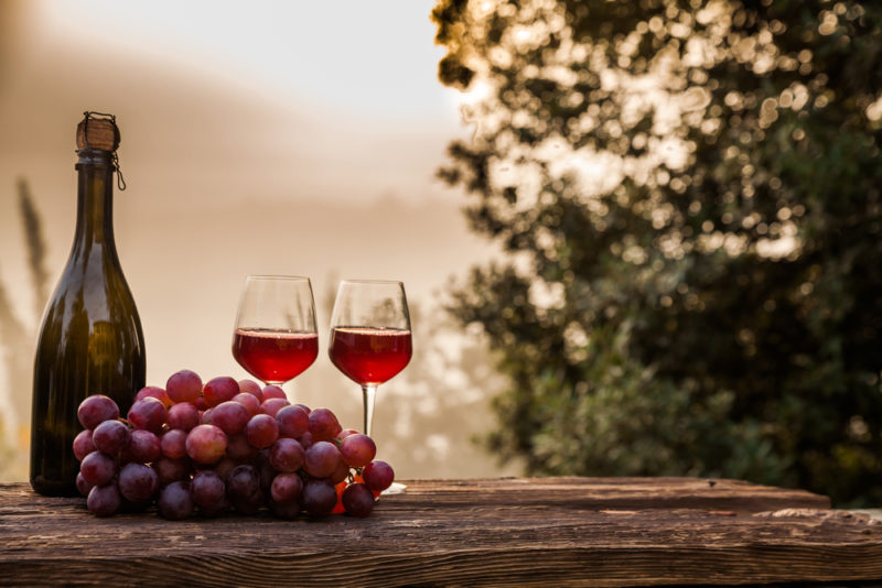 Two glasses of round Italian red wines outside next to a bunch of grapes and a bottle of wine