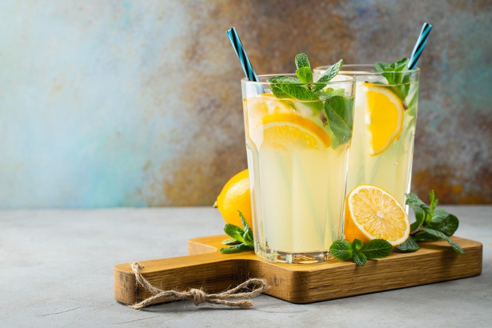 Two glasses of spiked lemonade with straws and lemonson a wooden plank