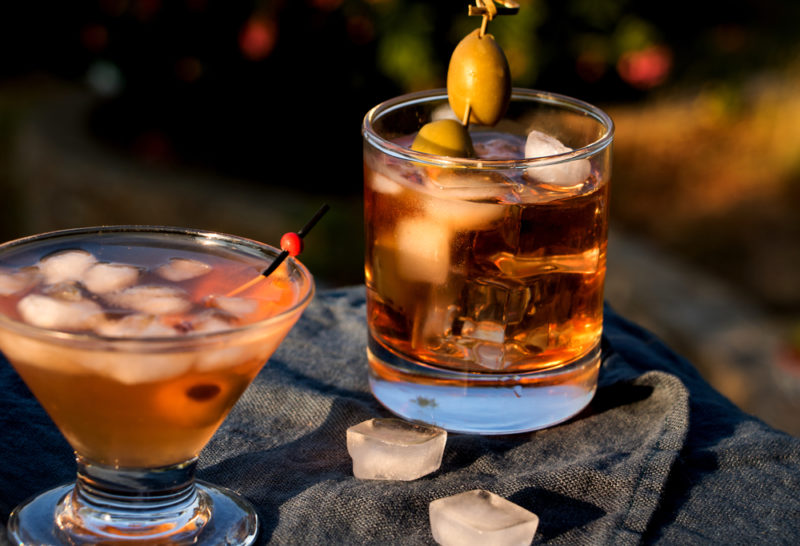 A wooden table with two different shaped glasses of sweet red vermouth on the rocks