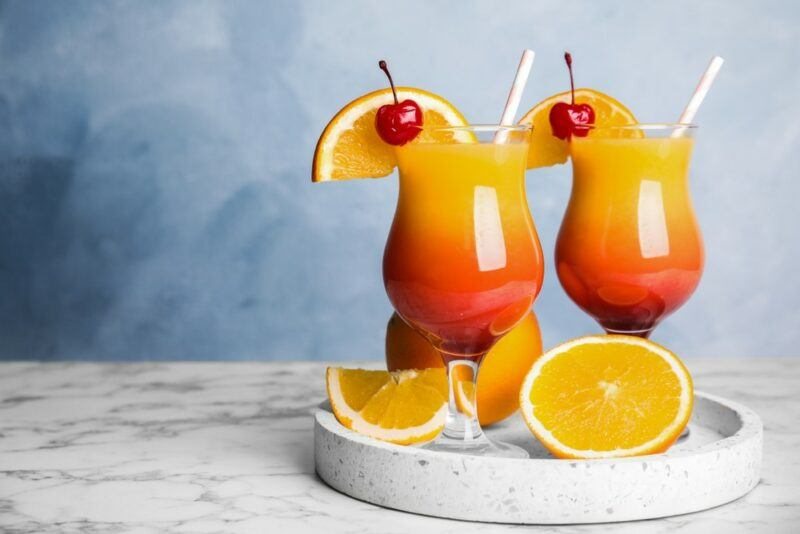 Two hurricane glasses filled with a tequila sunrise