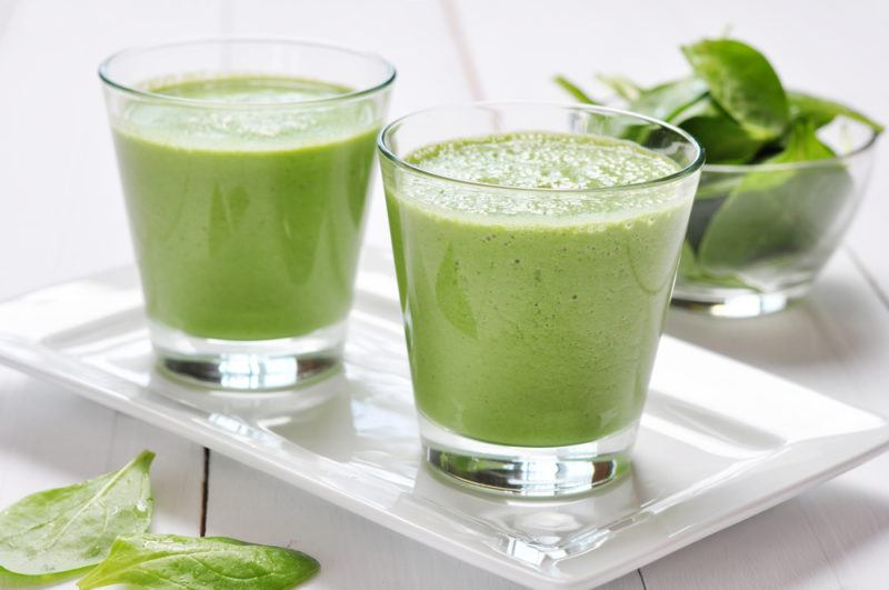 Two glasses of a green alkaline smoothie on a white plate with greens in the background