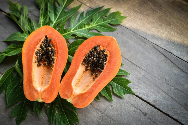 Two halves of a papaya against leaves from the tree