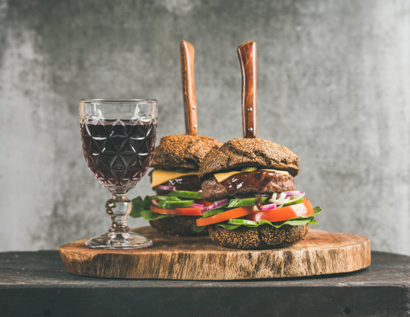 Two hamburgers on a wooden board, each with steaks through them, next to a glass of wine