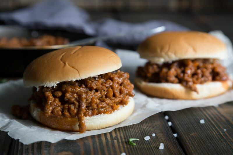Two sloppy joes made using burger buns on a table