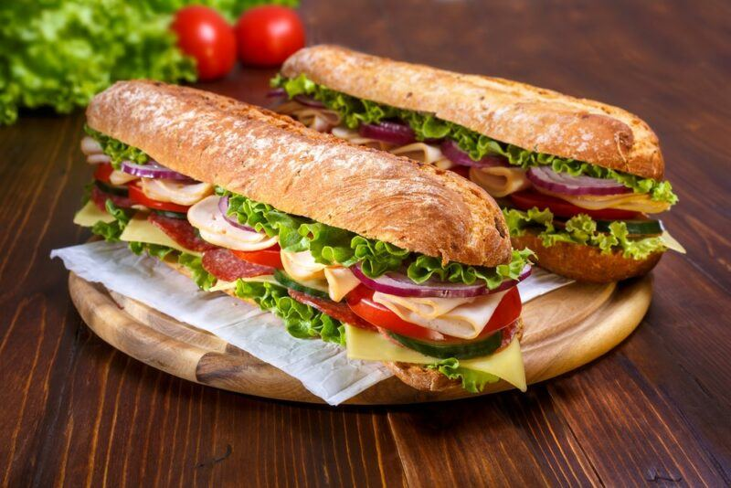 A wooden board with two large subway sandwiches with lettuce, tomatoes, and other fillings