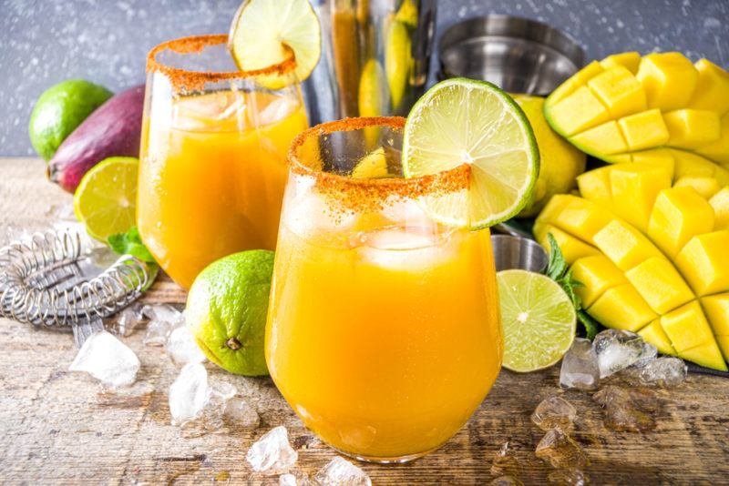Two mango margaritas in glasses with mangos, limes, ice, and other ingredients in the background