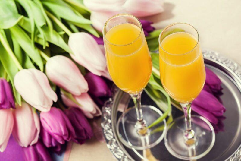 A metal tray of two mimosas next to purple and white tulips