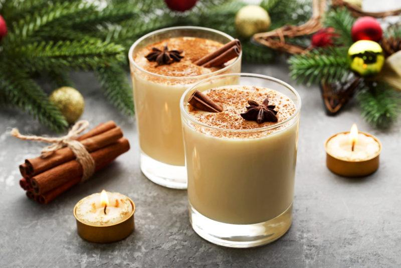 Two mugs of eggnog on a table with candles, part of a Christmas tree, and cinnamon