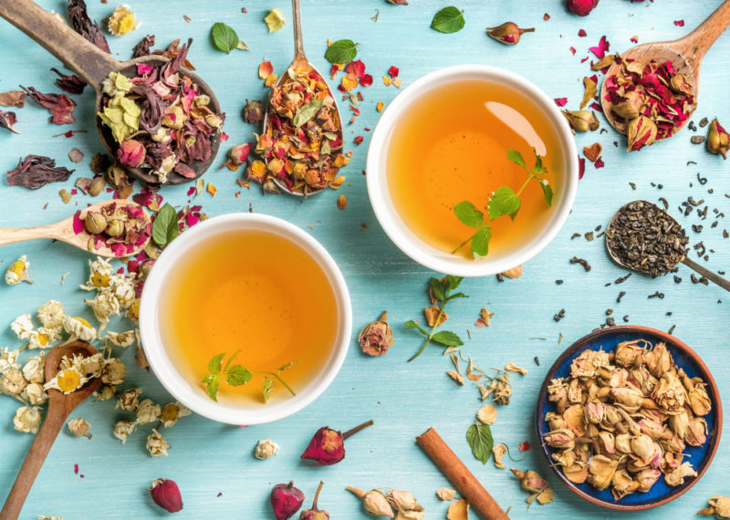 Two mugs of herbal tea next to herbs, flower petals and flower buds
