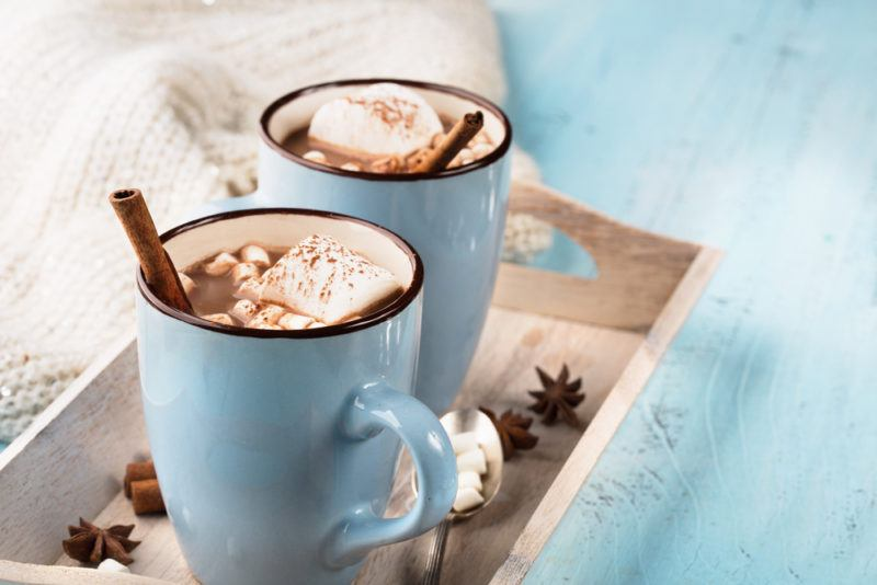 Two blue mugs of hot chocolate on a tray