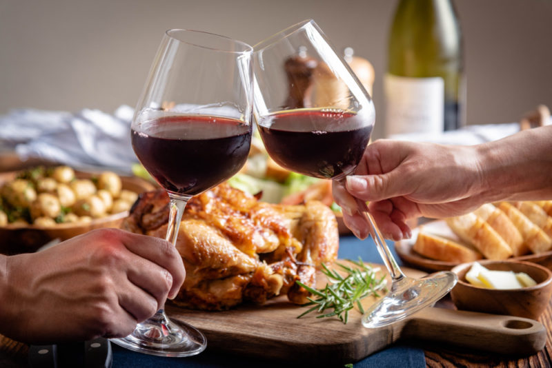 Two people clinking glasses of red wine together in front of a roast chicken dinner