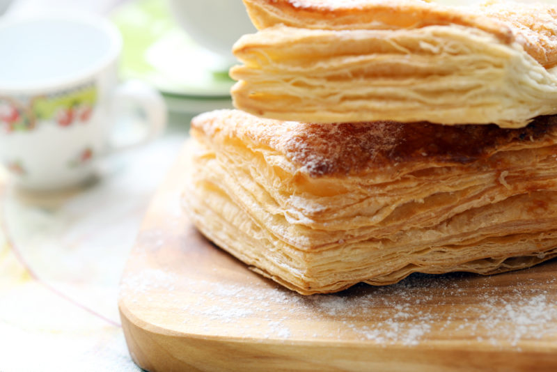 Two pieces of puff pastry with sugar on a wooden board