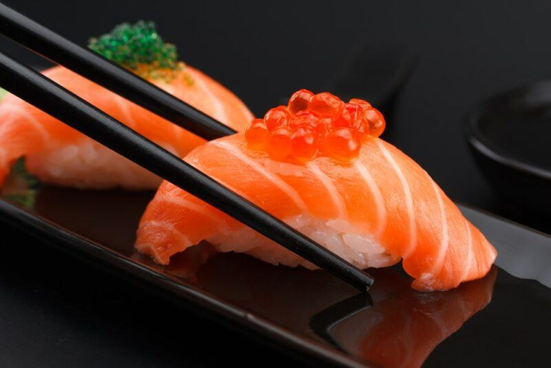 Two pieces of salmon sushi with fish roe, with a pair of black chopsticks