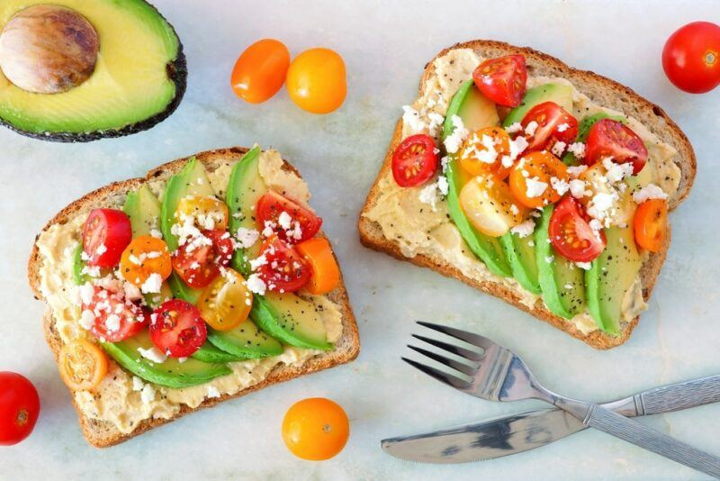 Two pieces of toast with hummus, avocados, and tomatoes