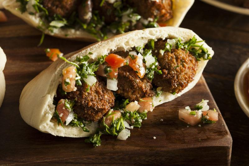 A pita pocket stuffed full with falafel and a variety of other ingredients