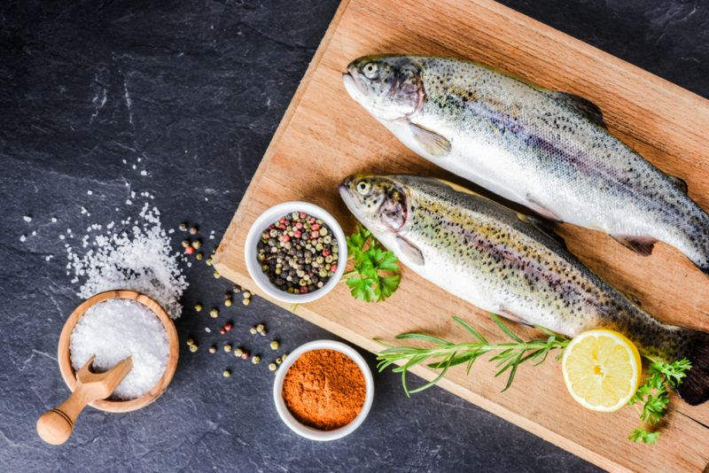 Two rainbow trout on a wooden board with small white bowls of seasoning and salt