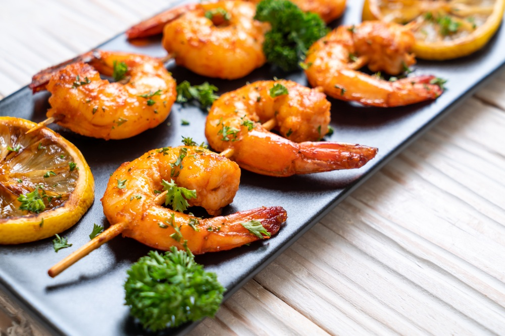 A black plate with two skewers of grilled shrimp, some parsley and a lemon slice