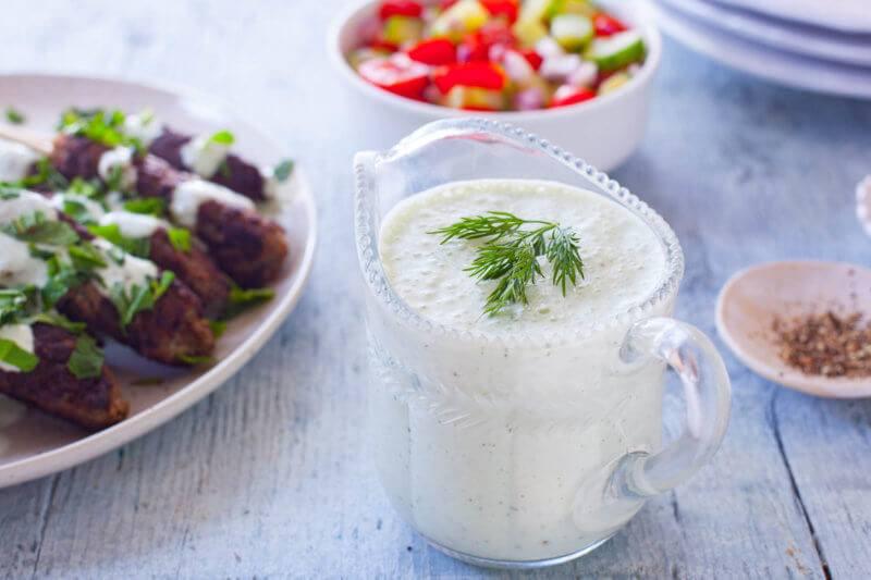 A glass jug of tzatziki sauce