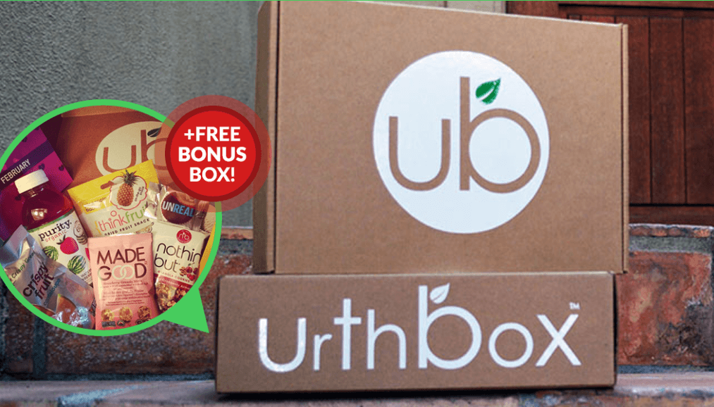 """2 Urth Boxes one set on top of the other, the front of the box on the top has UB and the bottom box side showing says UrthBox.  Off to the left there is a thought bubble with various vegetarian foods in it and a red dot with """"+Free Bonus Box!' written inside"""