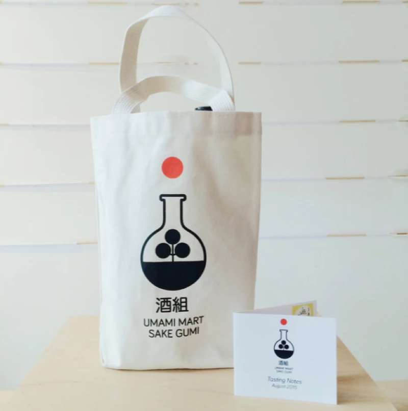 Off white background, whith a Umami mart sake gumi bag sitting on top with two bottles of sake and a tasting notes card sitting on the table in front of the bag