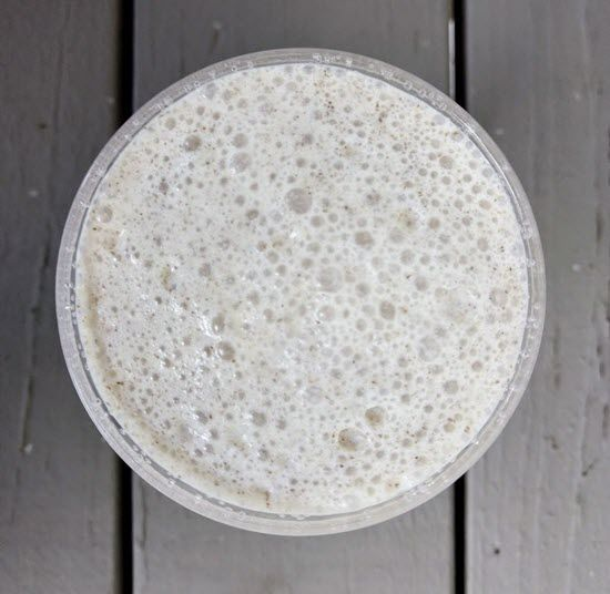 A top down image of a vanilla smoothie  on a wooden table.