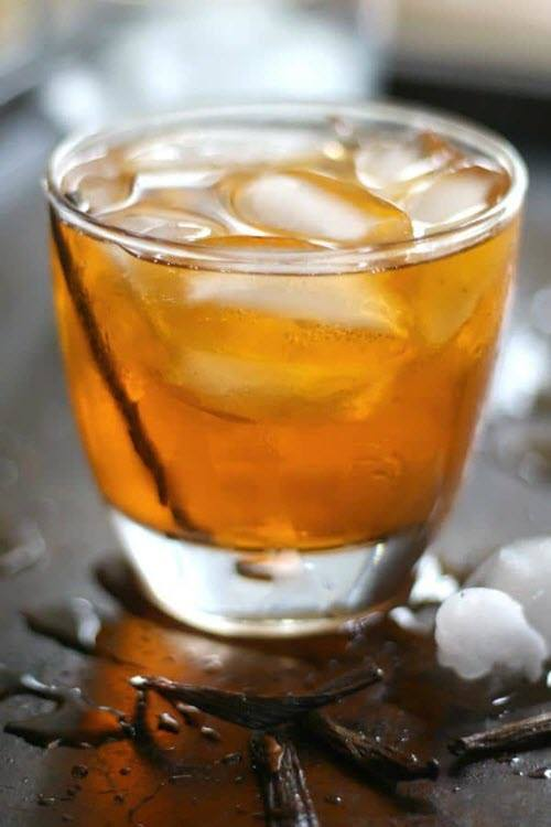 A short glass with a whisky cocktail and ice