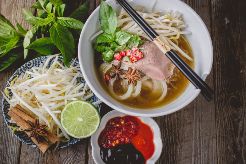 A large white bowl of Vietnamese pho soup next to sauces and other toppings
