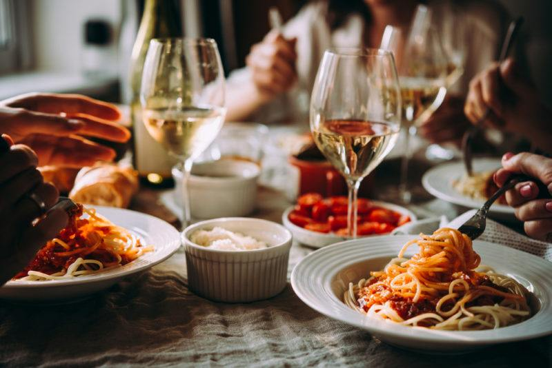 A table with white plates of pasta and glasses of wine