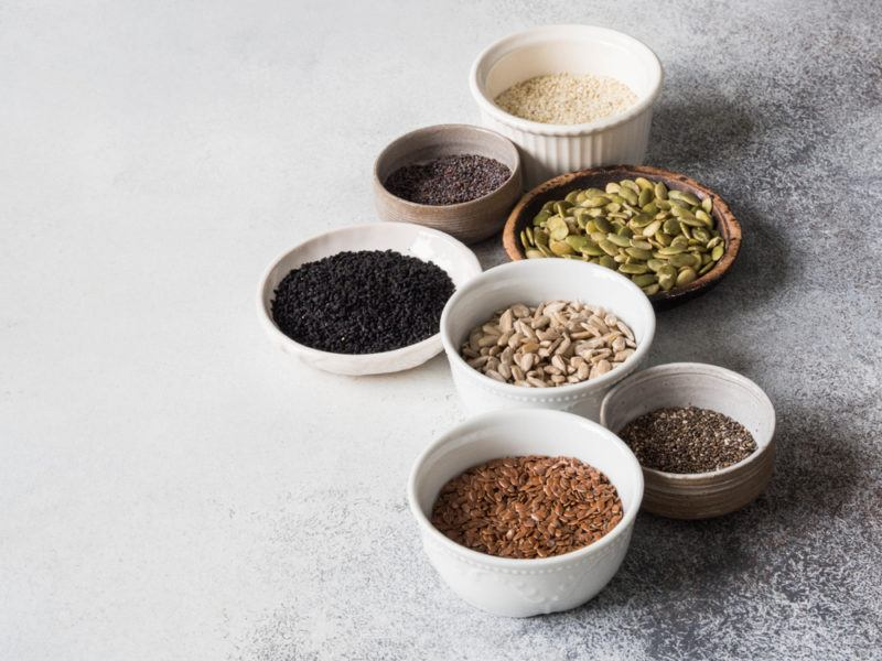 Small bowls filled with different types of seeds