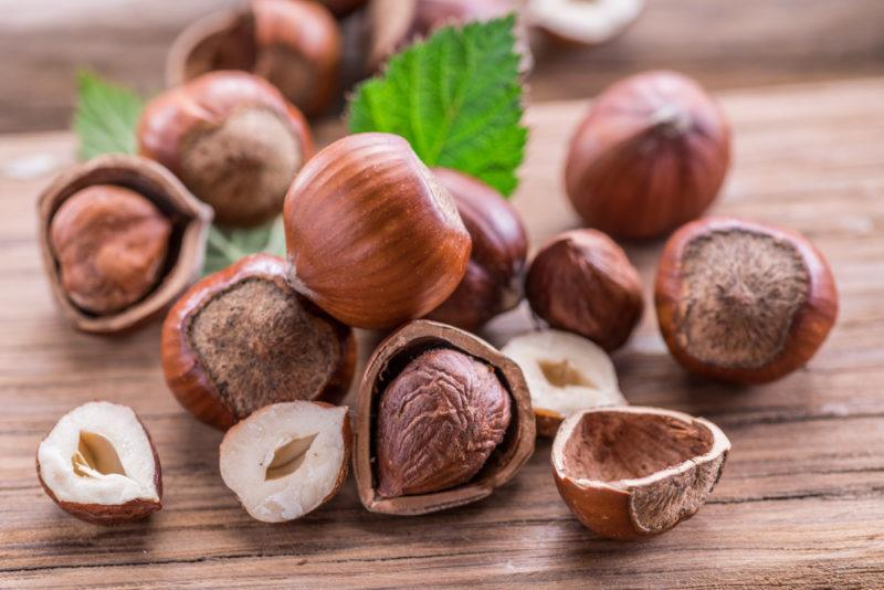 A selection of hazelnuts on a table. Some are whole, some have been opened or split and there are some leaves as well