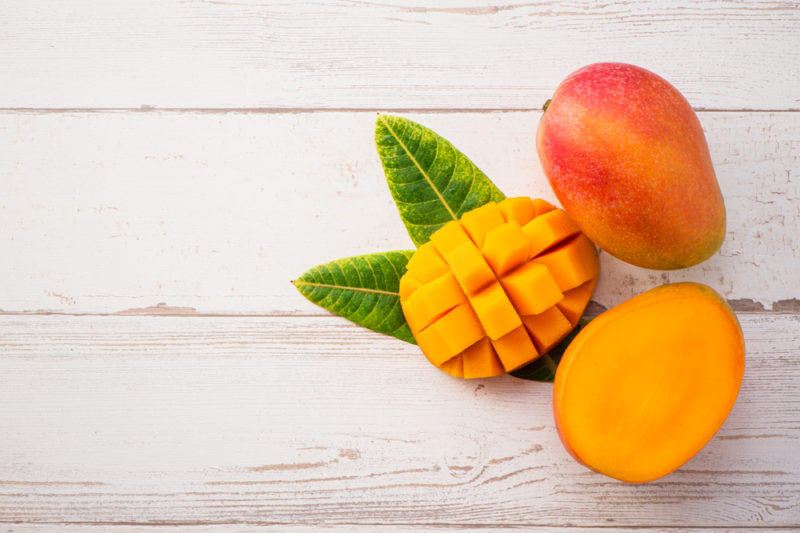 A white table with a whole mango, a half mango, and a mango that has been sliced into chunks